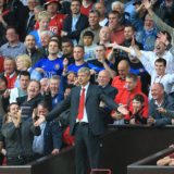 Arsenal's manager Arsene Wenger goes to the stands after being sent off the touchline by the referee